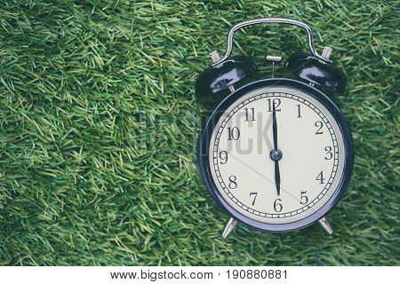 Times Retro Clock Lay On Green Grass Nature Face Timed At 6 O'clock Morning Time For Background Or P