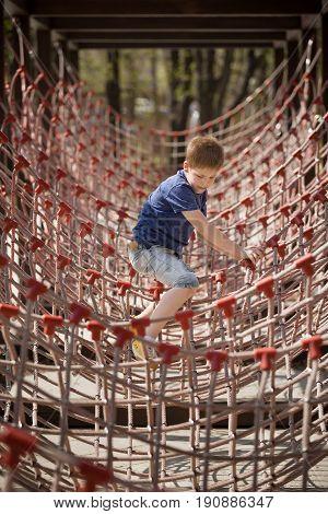 Cute kid boy climbing rope attraction outdoors. Active child walking in the park. School outdoor activities for children.