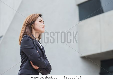 Asian Working Woman Think Or Business Girl Thinking With Building Architecture Background.
