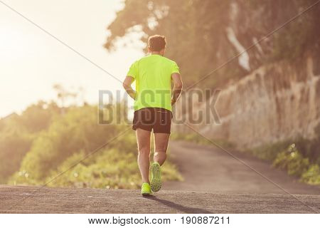 Jogging / running sneakers on the asphalt outdoors. Shallow focus on right shoe.
