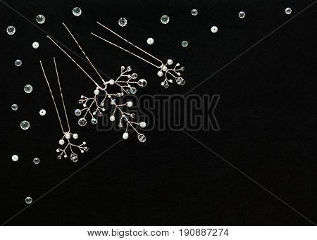 Handmade white gentle wedding bijouterie: hairpins with crystals branches decoration, lying flat on the horizontal black background, top view