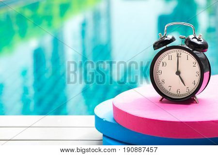 Swimming Times, Retro Black Bell Clock Time At 5 O'clock At Swimming Pool Blur Background.
