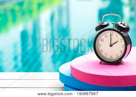 Swimming Times, Retro Black Bell Clock Time At 2 O'clock At Swimming Pool Blur Background.