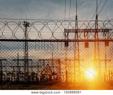 Metal wire fence and a sign of safety in the electrical substation.