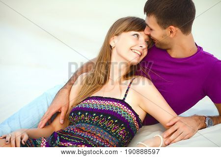 happy couple lying on sand in desert on romantic travel honeymoon vacation summer holidays romance. Young happy couple on the beach with white sand, caucasian woman and man embracing and looking in each other