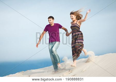 happy couple running from the mountain. couple on romantic travel honeymoon vacation summer holidays romance.