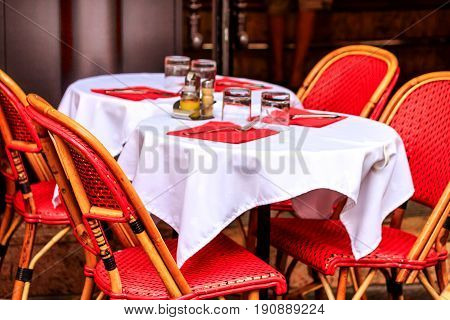 Table laid for lunch in a Parisian cafe with red wicker chairs