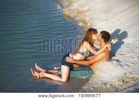 happy romantic lovers in travel honeymoon vacation summer holidays romance. inlove girl and man kissing on ocean shore