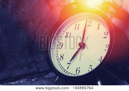 7 O'clock Vintage Clock At Dark Color Tone With Sun Light Memory Time Concept.