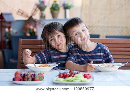 Cute Children, Preschool Boys, Eating Spaghetti For Lunch Outdoors In Garden
