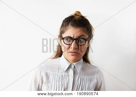 Portrait of skeptical Caucasian young entrepreneur female wearing white stripped shirt and eyeglasses looking aside with raised eyebrow. Young business woman with disgust and disapproval on her face