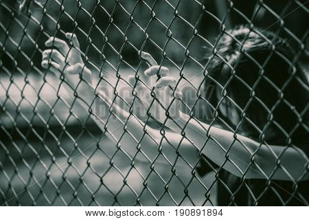 prison women in the cage hand at fence prison in jail no freedom struggle concept with grain texture.