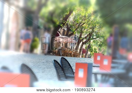 Artistic work of my own. Intentional blur at this design Narrow historic street with restaurant and cafes in the village of Valldemossa on Mallorca Spain