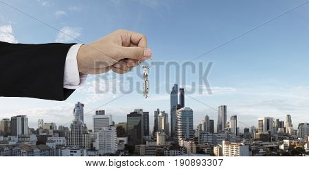 Hand holding keys with Bangkok city background, buying home, real estate and house rental concepts