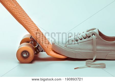 Side view of white sneaker stepping on hipster skateboard