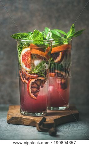Blood orange citrus lemonade with mint and ice in tall glasses, dark brown stone background. Refreshing summer drink concept