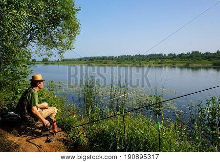Fisherman on a coast of river morning landscape