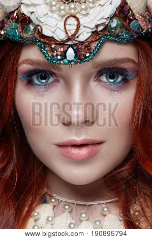 Redhead girl with bright makeup and big lashes. Mysterious fairy woman with red hair. Big eyes and colored shadows long lashes. Sexy look pure skin care care face