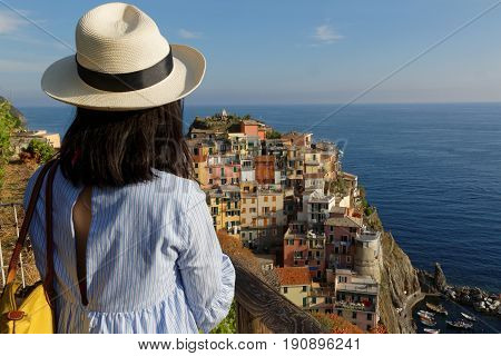 MANAROLA Italy June 2 2017 : A young woman admires a village of the Cinque Terre National Park on the Italian Riviera. The Cinque Terre area is a very popular tourist destination and a world heritage site.