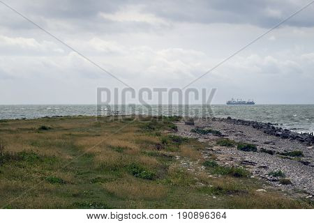 Danish coastline landscape close to Big Belt with a container cargo ship in a foggy background.