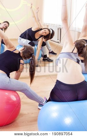 Sport Fitness Helathy Lifestyle Concepts. Group of Five Caucasian Female Athletes Having Stretching Exercises with Fitballs Indoors. Vertical Shot.