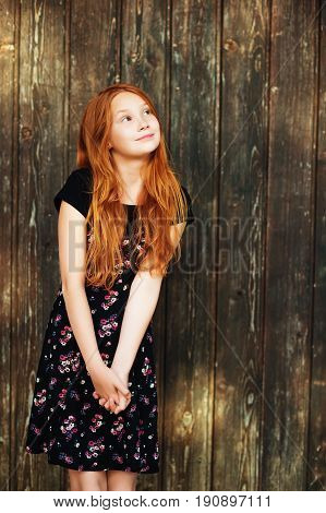 Outdoor fashion portrait of happy red-haired girl posing against old wooden background