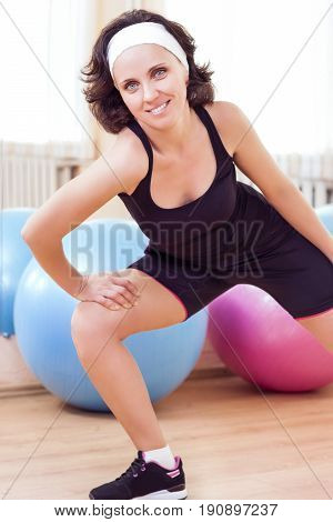 Sport Fitness Wellness and Lifestyle Ideas.Portrait of Female Caucasian Athlete In Good Fit Posing Against Fitballs in Gym. Vertical Image Composition