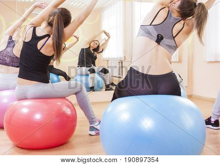 Sport Fitness Wellness and Helathy Lifestyle Concepts. Group of Five Caucasian Female Athletes Having Stretching Exercises with Fitballs Indoors.Horizontal Image