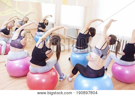 Fitness Wellness and Helathy Lifestyle Concepts. Group of Five Caucasian Female Athletes Having Stretching Exercises with Fitballs Indoors.Horizontal Shot
