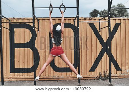 Suspension training. Full length rear view of young woman in sports uniform exercising outdoors