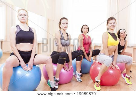 Sport and Fitness Concepts and Ideas. Group of Five Caucasian Female Athletes Having Exercises With Fitballs in Gym Together.Horizontal Image Orientation