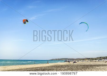 Kite surfers on calm italian beach Puglia