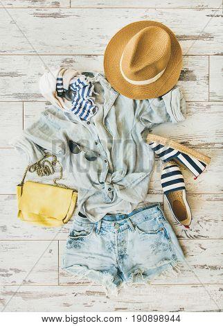 Summer outfit flatlay. Pastel summer women's clothes, parquet background, top view. Blue denim shorts, linen shirt, straw hat, yellow bag, sunglasses, blue and white striped neckerchief, espadrillas