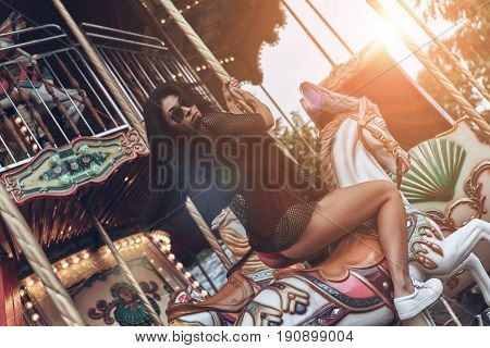 Going round. Attractive young mixed raced woman in red bikini riding merry-go-round