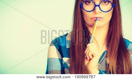 Studying education and fun concept. Nerdy thinking woman in weird big glasses holding pen. Studio shot on blue background