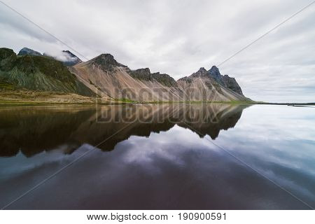 Amazing landscape of mountains reflected in the water the Bay. View of Cape Stokksnes in the southeastern part of Iceland, Europe. Art processing of photographs, color toning