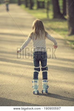 Small girl roller blading in the park, back turned to camera, moving fast
