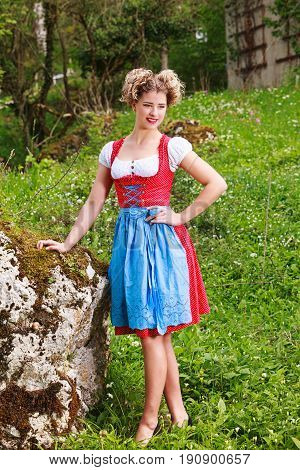 Blond young woman with extravagant hairstyle in dirndl on a meadow with rocks