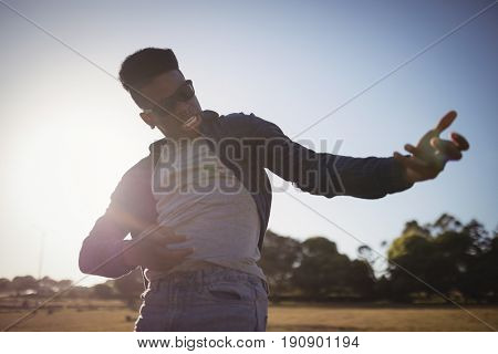 Close up of man gesturing while standing on field against clear sky