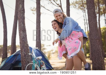Happy woman piggybacking man while standing at campsite