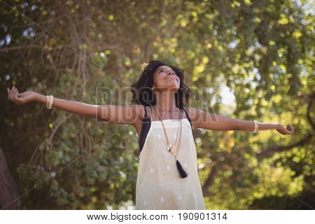 Smiling woman with arms outstretched standing against trees