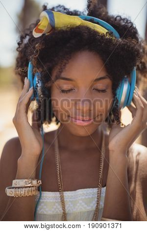 Close of young woman with eyes closed listening music at campsite