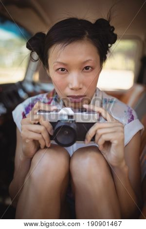 Portrait of woman holding camera while sitting in van