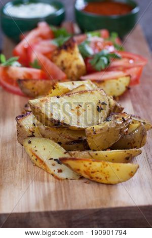 Spicy oven roasted potato wedges with tomato salad