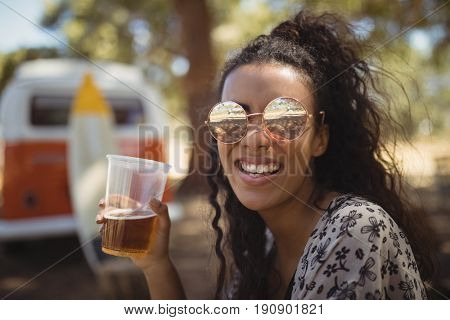 Happy young woman holding beer glass against van on field