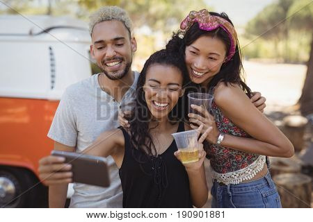 Smiling woman with friends taking selfie from mobile phone while standing by van on field