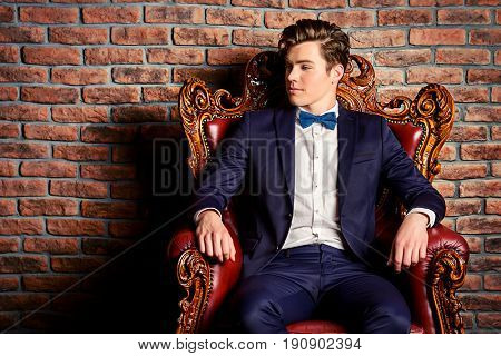 Portrait of a stylish handsome young man sitting in vintage armchair. Fashion shot. Men's clothing and accessories.