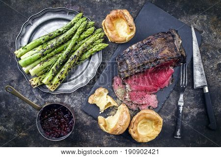 Barbecue dry aged Rib of Beef with green Asparagus and Yorkshire Pudding as close-up on an old metal sheet