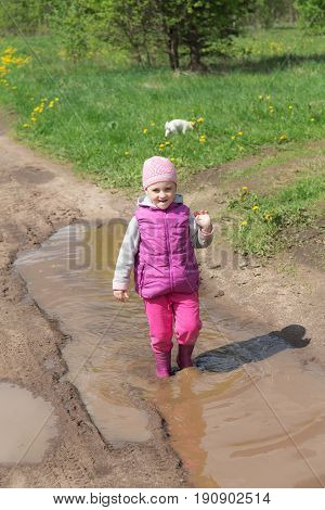 Little girl is walking in a puddle in spring