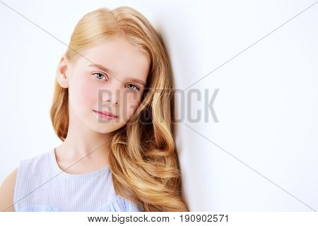 Beautiful little girl in a pale blue dress standing in a white room full of light. Kid's fashion. Hairstyle.